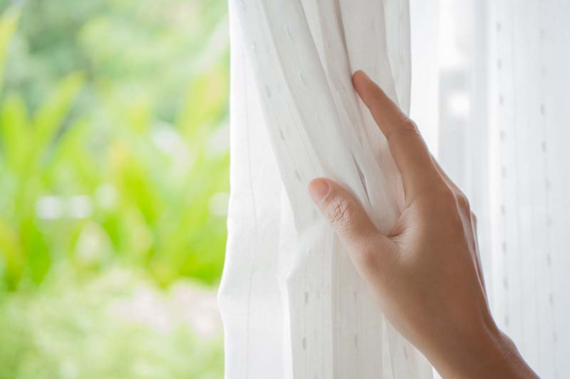 spring money, saving tips, Woman's hand opening curtains in the bedroom with natural light and garden background.